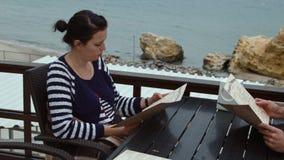 mujer 4K que mira el menú en un café cerca del mar, páginas de torneado y eligiendo las placas para la datación del acontecimient metrajes