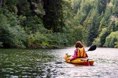 Mujer kayaking en el río en bosque Fotografía de archivo libre de regalías