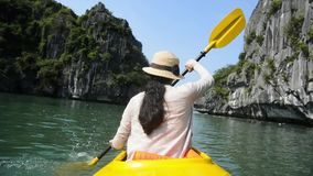 Mujer kayaking en la bahía de Halong, Vietnam metrajes