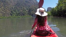 Mujer kayaking en la cámara hermosa pov de la acción de la laguna de la muchacha que se bate en el barco del kajak en el mar metrajes