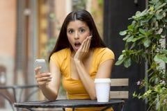 Mujer latina atractiva chocada en su teléfono elegante Imagen de archivo libre de regalías