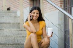 Mujer latina atractiva en sus años 20 felices hablando su teléfono elegante móvil Fotos de archivo libres de regalías
