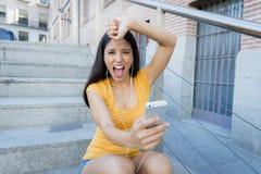 Mujer latina atractiva que escucha la música en su teléfono elegante Imágenes de archivo libres de regalías
