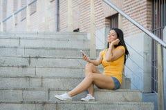 Mujer latina atractiva que escucha la música en su teléfono elegante Imagen de archivo libre de regalías