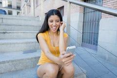 Mujer latina atractiva que escucha la música en su teléfono elegante Foto de archivo libre de regalías