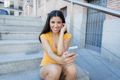 Mujer latina atractiva que escucha la música en su teléfono elegante Imagenes de archivo