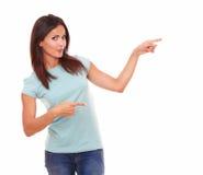 Mujer latina atractiva que señala a su izquierda Fotos de archivo