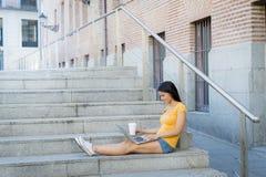Mujer latina atractiva que trabaja en su ordenador portátil Foto de archivo libre de regalías