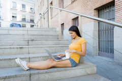 Mujer latina atractiva que trabaja en su ordenador portátil Foto de archivo