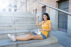 Mujer latina atractiva que trabaja en su ordenador portátil Imagenes de archivo