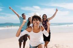 Mujer latina de risa con animar a adultos jovenes en la playa Fotografía de archivo libre de regalías
