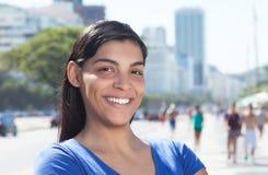 Mujer latina de risa con el pelo oscuro largo en la ciudad Foto de archivo libre de regalías