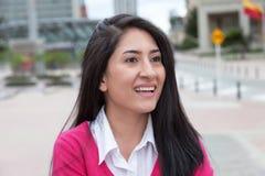 Mujer latina de risa con un chaleco rosado afuera en la ciudad Foto de archivo