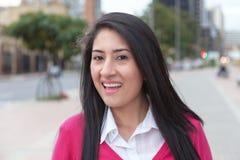 Mujer latina feliz con un chaleco rosado afuera en la ciudad Fotografía de archivo