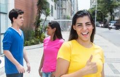 Mujer latina hermosa con la camisa y los amigos amarillos en la ciudad Foto de archivo libre de regalías
