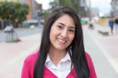 Mujer latina hermosa con un chaleco rosado afuera en la ciudad Foto de archivo libre de regalías
