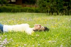 Mujer latina hermosa feliz que miente en la hierba verde que duerme y que medita imagenes de archivo