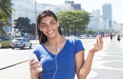 Mujer latina hermosa que escucha la música con el teléfono Foto de archivo libre de regalías