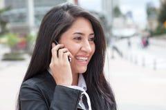 Mujer latina hermosa que habla en el teléfono en la ciudad Imagenes de archivo