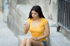 Mujer latina joven atractiva chocada y sorprendida que manda un SMS y que habla en su teléfono celular elegante Imagen de archivo libre de regalías