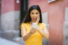 Mujer latina joven atractiva chocada y sorprendida que manda un SMS y que habla en su teléfono celular elegante Imágenes de archivo libres de regalías