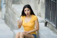 Mujer latina joven atractiva chocada y sorprendida que manda un SMS y que habla en su teléfono celular elegante Foto de archivo libre de regalías