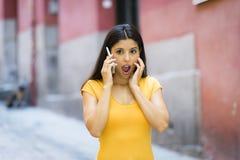 Mujer latina joven atractiva chocada y sorprendida que manda un SMS y que habla en su teléfono celular elegante Imagenes de archivo