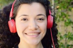 Mujer latina joven con los auriculares en un parque Imagen de archivo