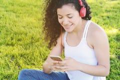 Mujer latina joven con los auriculares en un parque Foto de archivo