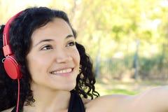Mujer latina joven con los auriculares en un parque Imágenes de archivo libres de regalías