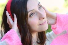 Mujer latina joven con los auriculares en un parque Fotos de archivo libres de regalías