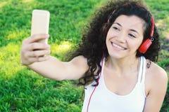 Mujer latina joven con los auriculares en un parque Fotos de archivo