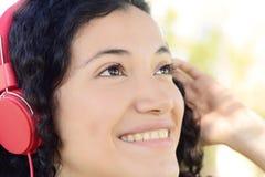 Mujer latina joven con los auriculares en un parque Imagenes de archivo