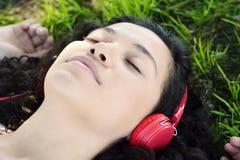 Mujer latina joven con los auriculares en un parque Foto de archivo libre de regalías