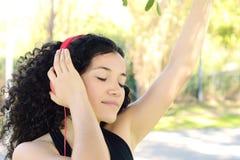 Mujer latina joven con los auriculares en un parque Imagen de archivo libre de regalías