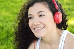 Mujer latina joven con los auriculares en un parque Fotografía de archivo libre de regalías