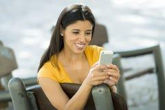 Mujer latina joven feliz que habla y que manda un SMS en el teléfono elegante Foto de archivo