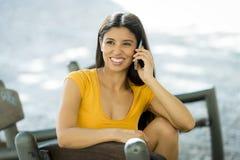 Mujer latina joven feliz que habla y que manda un SMS en el teléfono elegante Fotos de archivo libres de regalías