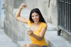 Mujer latina joven feliz que habla y que manda un SMS en el teléfono elegante Fotos de archivo