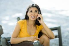 Mujer latina joven feliz que habla y que manda un SMS en el teléfono elegante Fotografía de archivo