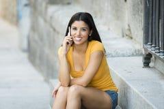 Mujer latina joven feliz que habla y que manda un SMS en el teléfono elegante Foto de archivo libre de regalías