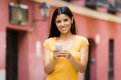 Mujer latina joven feliz que habla y que manda un SMS en el teléfono elegante Imágenes de archivo libres de regalías