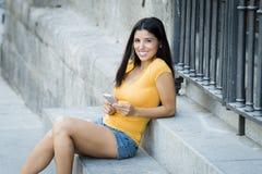 Mujer latina joven feliz que habla y que manda un SMS en el teléfono elegante Imagen de archivo libre de regalías