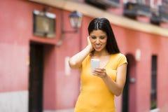 Mujer latina joven feliz que habla y que manda un SMS en el teléfono elegante Fotografía de archivo libre de regalías