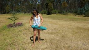 Mujer latina joven que abre la estera de la yoga en el parque Fotos de archivo libres de regalías