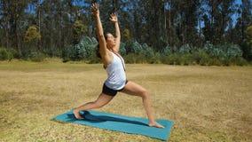 Mujer latina joven que hace yoga en el parque Foto de archivo