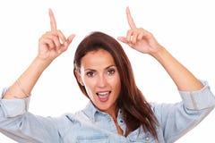 Mujer latina joven que señala encima de sus fingeres Foto de archivo