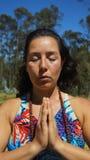 Mujer latina joven que se sienta haciendo yoga Fotos de archivo libres de regalías