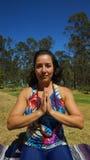 Mujer latina joven que se sienta haciendo yoga Imagen de archivo