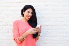 Mujer latina joven que usa su teléfono móvil Fotos de archivo